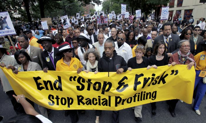 The Rev. Al Sharpton (C) walks with demonstrators during a silent march to end the stop-and-frisk program in New York, June 17, 2012. Mayor Bill de Blasio ended a court challenge Wednesday to a racial profiling law started under the previous administration. (Seth Wenig/AP)