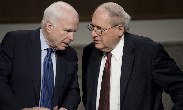 U.S. Democratic Sen. Carl Levin (R) of Michigan speaks with Republican Sen. John McCain of Arizona on Capitol Hill on Feb. 26, 2014. (Saul Loeb/AFP/Getty Images)