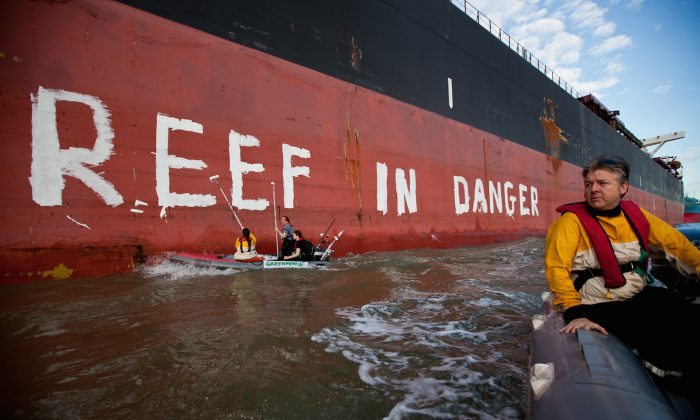 Activists paint the message 'Reef in Danger' on the side of coal ship Chou San on March 7, 2012 in Gladstone, Queensland. (Greenpeace via Getty Images)