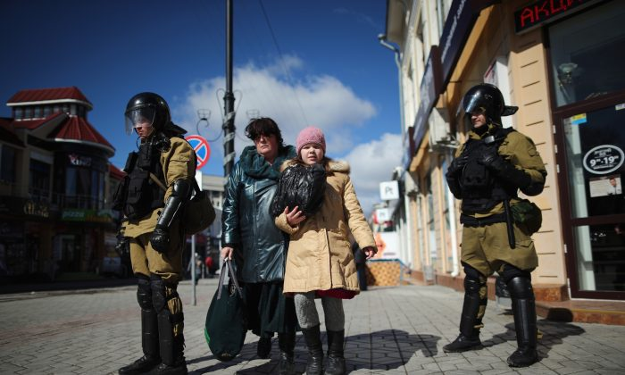 Members of the public walk between a line of Russian and Ukrainian Berkut riot police in Simferopol, Crimea, Monday. (Dan Kitwood/Getty Images)