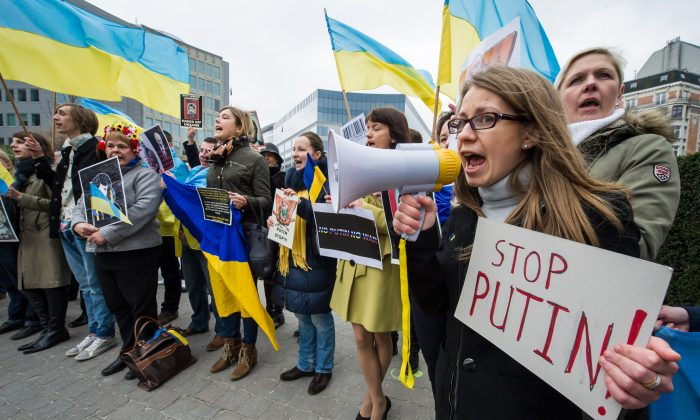 Pro-Ukrainian activists shout slogans as they demonstrate during an EU foreign ministers meeting outside the EU Council in Brussels, Monday. (AP Photo/Geert Vanden Wijngaert)