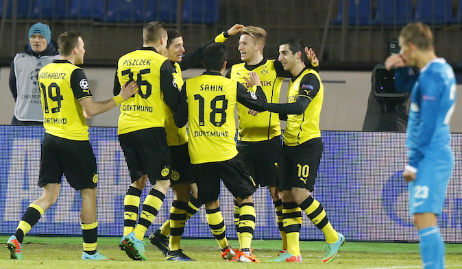 Zenit's Andrey Arshavin, right, watches as Borussia's Henrikh Mkhitaryan, center right, and other team players celebrate their goal against Zenit during the Champions League soccer match between Zenit St.Petersburg and  Borussia Dortmund at Petrovsky stadium in St.Petersburg, Russia, on Tuesday, Feb. 25, 2014. (AP Photo/Dmitry Lovetsky)