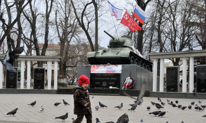 A boy with Russian flag ribbon walks in front of a monument displaying a T-34 tank in Simferopol, Crimea, on March 2, 2014. (Genya Savilov/AFP/Getty Images)