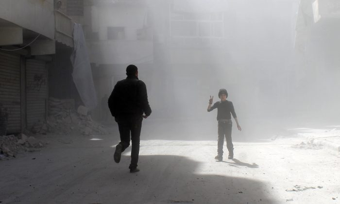 A Syrian boy amid dust as a man runs in a street of the northern city of Aleppo following a reported Syrian government forces airstrike on Feb. 21, 2014. (Baraa al-Halabi/AFP/Getty Images)