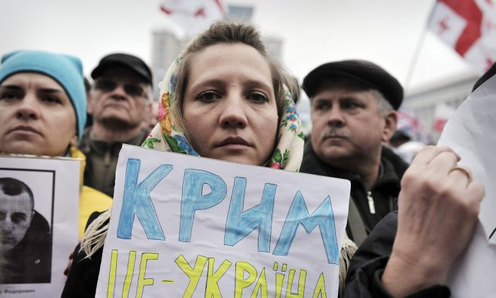 A woman holds a placard reading 'Crimea is Ukraine' while people attend a rally against Russia on Kyiv's Independence square March 2, 2014. (Louisa Gouliamaki/AFP/Getty Images)