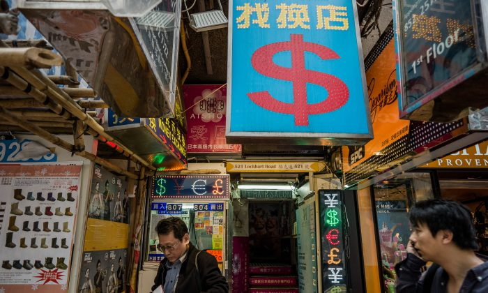 A man (L) leaves a currency exchange booth in Hong Kong on November 22, 2012. (Philippe Lopez/AFP/Getty Images)