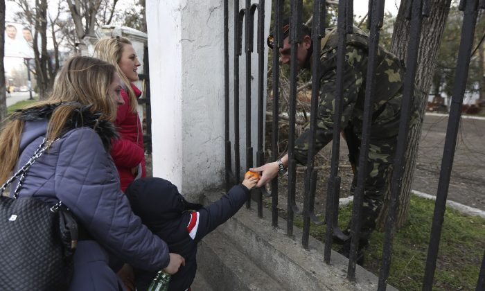 A child gives fruit to a Ukrainian officer  (AP Photo/Maxin Vetrov)