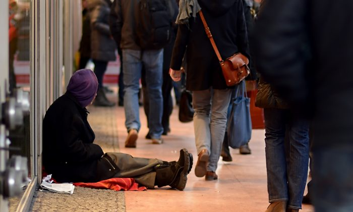 """A man begging for money sits on the pavement in Berlin, on Dec. 20, 2012. Some Romanians are being lured to Germany on false promises to beg on the streets for """"employers."""" (Britta Pedersen/AFP/Getty Images)"""