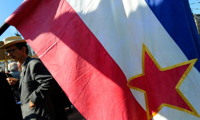 A man behind the flag of the former communist Yugoslavia attends a celebration of the May Day in Belgrade, on May 1, 2010. On the eve of the 30th anniversary of Tito's death many of his followers gather on various places remembering of past era. (Andrej Isakovic/AFP/Getty Images)