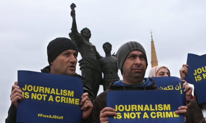 Two Lebanese cameramen who work for Al Jazeera hold placards to show their solidarity with journalists detained by Egyptian authorities during a sit-in in downtown Beirut on Feb. 27, 2014. Egyptian-Canadian journalist Mohamed Fahmy is on trial in Egypt with two Al-Jazeera English journalists and 17 other defendants on terrorism-related charges. (AP Photo/Hussein Malla)
