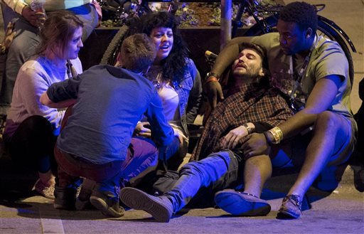 Unidentified people are comforted after being struck by a vehicle on Red River Street in downtown Austin, Texas, during SXSW on Wednesday March 12, 2014. Police say two people were confirmed dead at the scene after a car drove through temporary barricades set up for the South By Southwest festival and struck a crowd of pedestrians.  (AP Photo/Austin American-Statesman, Jay Janner)