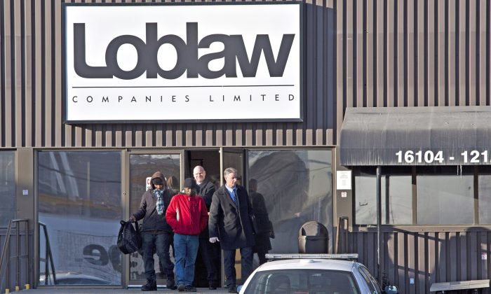 Police detectives walk out with witnesses as they investigate the scene where two people were killed and four people were injured after a stabbing at a Loblaw warehouse in Edmonton on Feb. 28, 2014. (The Canadian Press/Jason Franson)
