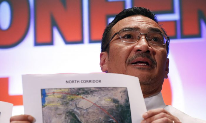 Malaysia's acting Transport Minister Hishamuddin Hussein shows maps of northern search corridor during a press conference at a hotel near the Kuala Lumpur International Airport, in Sepang, Malaysia, Monday, March 17, 2014. Twenty-six countries are involved in the massive international search for the Malaysia Airlines jetliner that disappeared on March 8 with 239 people aboard. They include not just military assets on land, at sea and in the air, but also investigators and the specific support and assistance requested by Malaysia, such as radar and satellite information. (AP Photo/Vincent Thian)