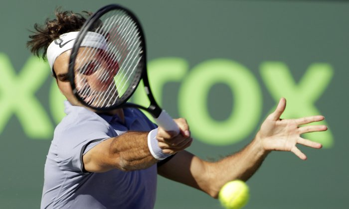 Roger Federer, of Switzerland, returns the ball to Richard Gasquet, of France, during the Sony Open tennis tournament, Tuesday, March 25, 2014, in Key Biscayne, Fla. (AP Photo/Luis M. Alvarez)