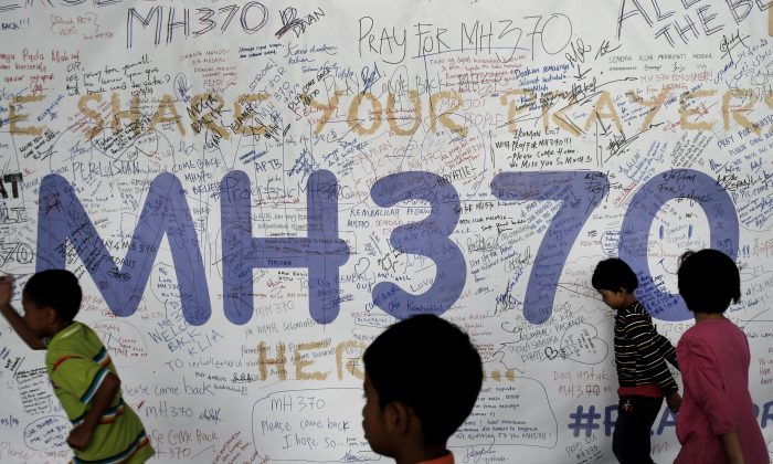 Children run past dedication messages and well wishes displayed for passengers and others involved with the missing Malaysia Airlines jetliner MH370 on the walls of the Kuala Lumpur International Airport, Thursday, March 13, 2014,  in Sepang, Malaysia. (AP Photo/Wong Maye-E)
