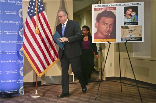 "George Venizelos, left, the FBI assistant director of the New York field office, and Loretta Lynch, center, U.S. Attorney for the Eastern District of New York, walks past a display showing Juan Elias Garcia, left, and his alleged murder victims Vanessa Argueta and her son Diego Torres, right, at a press conference, Wednesday March 26, 2014 in New York. The FBI announced that Garcia, 21, has been added to the their ""Ten Most Wanted Fugitives"" list for his alleged role in the 2010 slayings of his 19-year-old girlfriend and her 2-year-old son on Long Island in New York. The FBI said that the Salvadoran is the last of four MS-13 gang members being sought in the killings. (AP Photo/Bebeto Matthews)"