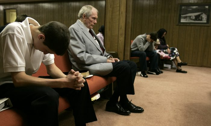 FILE - In this March 19, 2006 file photo, the Rev. Fred Phelps Sr., center, sits in prayer at his Westboro Baptist Church in Topeka, Kan. (AP Photo/Charlie Riedel, File)