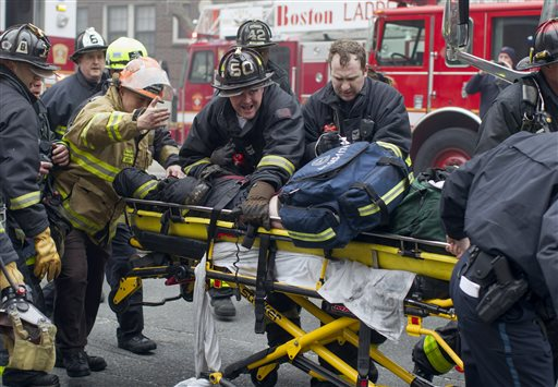 Firefighters and emergency medical personnel rush a firefighter from the scene of a multi-alarm fire at a four-story brownstone in the Back Bay neighborhood near the Charles River, Wednesday, March 26, 2014, in Boston. Boston EMS spokesman Nick Martin says four people, including at least three firefighters, have been taken to hospitals. (AP Photo/Scott Eisen)