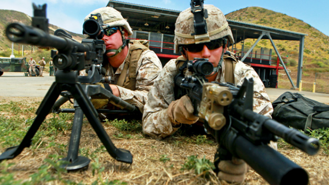 Marine Corps Lance Cpls. Benjamin V. Stout assists Lance Cpl. Josh M. Tasior as they hold security on the outer cordon of a target site during a Maritime Raid Force training course on Camp Pendleton, California. (Defense.gov)