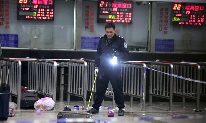 A Chinese police investigator inspects the scene of an attack at the train station in Kunming, southwest China's Yunnan province, on March 2, 2014, the day after over 10 attackers stabbed 29 people to death, and injured over 140 people. (STR/AFP/Getty Images)