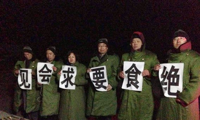 Six Chinese lawyers hold banners in front of the Qinglong Detention Center in Jiansanjiang City, Heilongjiang Province on March 25. Lawyers began a hunger strike after the detention center refused to allow them to visit illegally detained rights lawyers. (Li Jinxing)