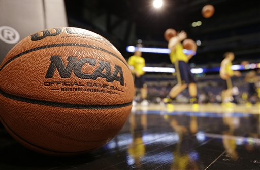 Michigan players shoot during practice for their NCAA Midwest Regional semifinal college basketball tournament game Thursday, March 27, 2014, in Indianapolis. Michigan plays Tennessee on Friday, March 28, 2013. (AP Photo/Michael Conroy)