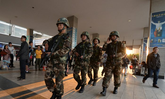 Chinese paramilitary police patrol outside the scene of the terror attack at the main train station in Kunming, Yunnan Province, on March 3, 2014. Discrimination against Uyghurs subsequent to the attack brought a response from some members of the Chinese public. (Mark Ralston/AFP/Getty Images)