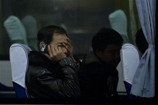 A relative of Chinese passengers aboard missing Malaysia Airlines Flight MH370 rubs his eyes as he talks on his mobile phone while waiting on a bus at a hotel in Beijing, Monday, March 10, 2014. Almost three days after the plane with 239 people on board vanished en route from Kuala Lumpur to Beijing, no debris has been spotted in Southeast Asian waters, hampering efforts to begin the investigation into how the plane disappeared. (AP Photo/Alexander F. Yuan)