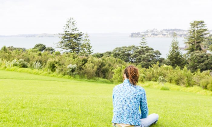 A woman sits alone and feels depressed in a public park overlooking the sea. (*Shutterstock)
