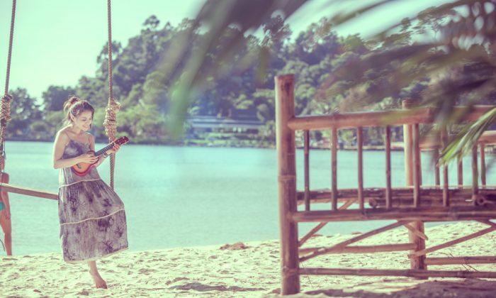 Playing ukulele on sunlit beach. (Shutterstock*)