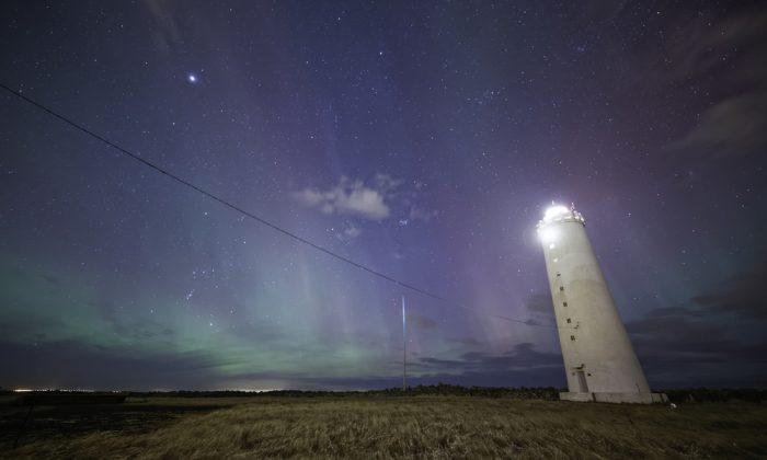 Iceland lighthouse under colorful aurora. (*Shutterstock)