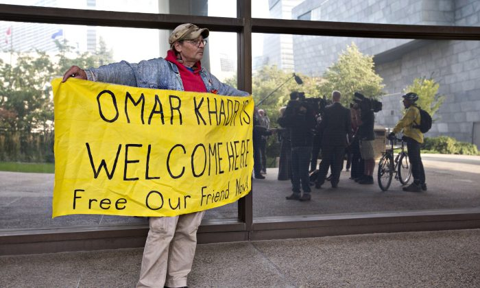 A supporter holds a sign outside the Edmonton courthouse during Omar Khadr's court appearance in Edmonton on Sept. 23, 2013. The former Guantanamo Bay inmate is recuperating after surgery for a wound he incurred in Afghanistan 12 years ago. (The Canadian Press/Jason Franson)