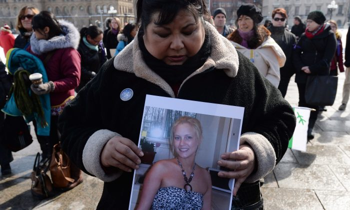 Ottawa resident Sharon Armstrong takes part in a vigil on Parliament Hill on Wednesday, March 5, 2014, for murdered Inuit student Loretta Saunders. Speakers at the vigil called for a national inquiry into missing and murdered aboriginal women. (The Canadian Press/Sean Kilpatrick)