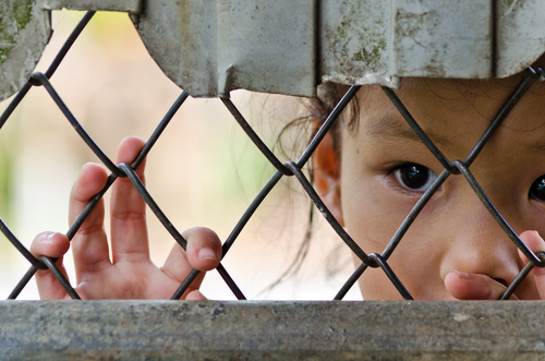 A child stare longingly from behind a fence. (Shutterstock)