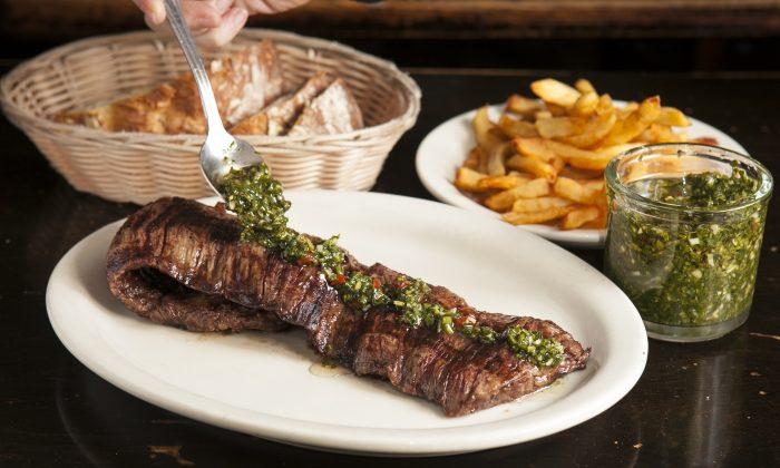Drizzling chimichurri sauce on the skirt steak. (Samira Bouaou/Epoch Times)