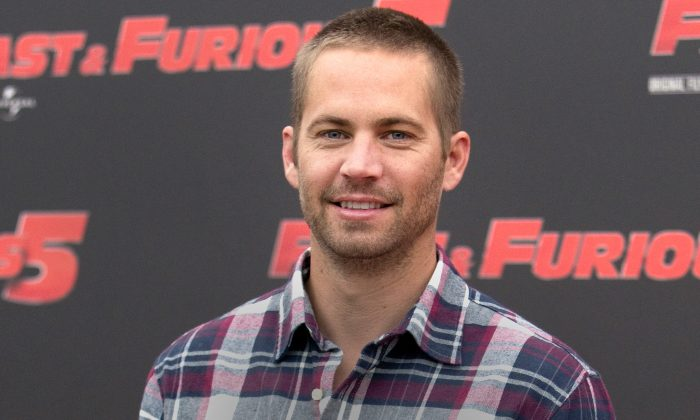 """In this April 29, 2011 file photo, actor Paul Walker poses during the photo call of the movie """"Fast and Furious 5,"""" in Rome. Walker's brothers are filling in to help finish shooting on """"Fast & Furious 7."""" Universal Pictures announced Tuesday, April 15, 2014, that Caleb and Cody Walker are filling in for their late brother to complete some remaining filming. Production has resumed on """"Fast & Furious 7"""" after it was suspended following Walker's death in late November. (AP Photo/Andrew Medichini, File)"""