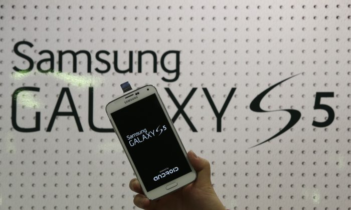 "An employee shows Samsung's Galaxy S5 smartphone at a mobile phone shop in Seoul, South Korea, in this March 27, 2014 file photo. Samsung Electronics will add two safeguards to its latest smartphone in an effort to deter rampant theft of the mobile devices nationwide, the company said Friday April 4, 2014. The world's largest mobile-phone maker said users will be able to activate for free its ""Find My Mobile"" and ""Reactivation Lock"" anti-theft features to protect the soon-to-be-released Galaxy 5 S.  (AP Photo/Lee Jin-man, File)"