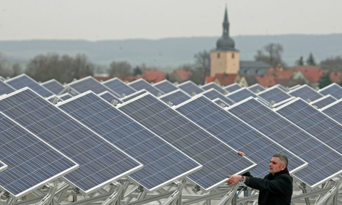 FILE - In this Nov. 19, 2008 file photo Roberto Chudzinski checks solar modules on the roof of the Soemtron AG in Soemmerda, Germany. After concluding that global warming is almost certainly man-made and poses a grave threat to humanity, the U.N.-sponsored expert panel on climate change is moving on to the next phase: what to do about it. The Intergovernmental Panel on Climate Change, or IPCC, will meet next week in Berlin to chart ways in which the world can curb the greenhouse gas emissions that scientists say are overheating the planet.  (AP Photo/Jens Meyer, File)
