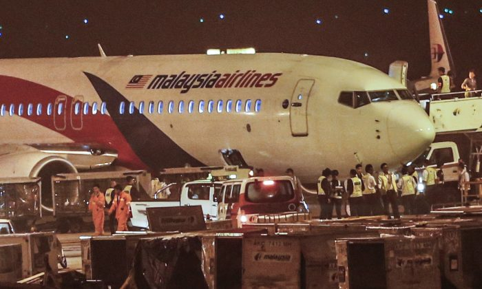 Ground crew check the Malaysia Airlines flight MH192 bound for Bangalore that turned back towards and parked at Kuala Lumpur International Airport in Sepang, Malaysia, Monday, April 21, 2014, after its right landing gear malfunctioned upon takeoff. The airline says Flight 192 carrying 166 people landed safely at the Kuala Lumpur International Airport early Monday, four hours after it departed. (AP Photo/Vincent Thian)