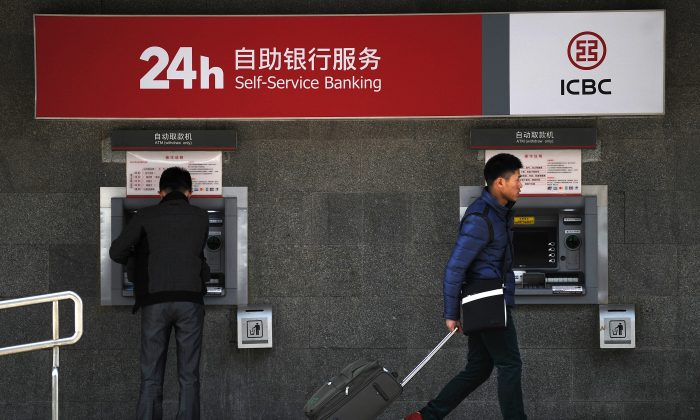 A man walks past an ATM machine at the entrance of a bank in Beijing, Jan 25.  (WANG ZHAO/AFP/Getty Images)