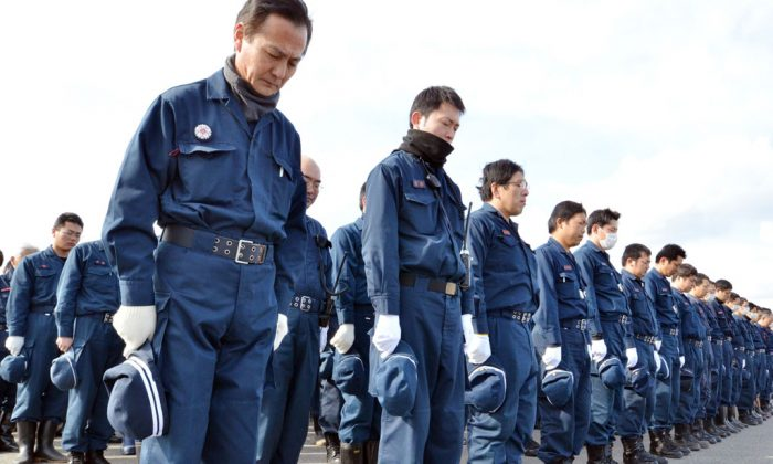 Police officers bow to offer prayers in silence for the victims in Namie, near the striken TEPCO Fukushima Dai-ichi nuclear plant in Fukushima prefecture on March 10, 2014, one day before the third anniversary of March 11 massive earthquake and tsunami. The 9.0 magnitude earthquake in 2011 sent a huge wall of water into the coast of the Tohoku region, splintering whole communities, ruining swathes of prime farmland and killing nearly 19,000 people. (Yoshikazu Tsuno/AFP/Getty Images)