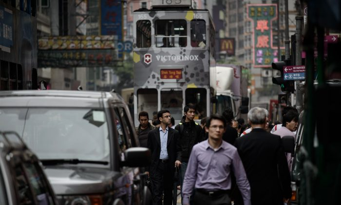 Pedestrians walk between cars and trams in a busy street of Hong Kong on April 1, 2014. China has been quietly picking away at the democracy and freedom promised Hong Kong; the international community gave its blessings to the deal, but will it react to China's reneging? (Philippe Lopez/AFP/Getty Images)