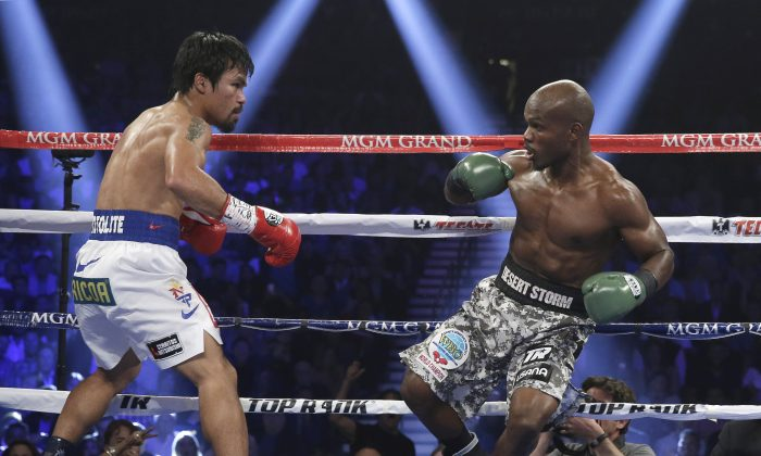 Manny Pacquiao, left, and Timothy Bradley in their WBO welterweight title boxing fight Saturday, April 12, 2014, in Las Vegas. (AP Photo/Isaac Brekken)