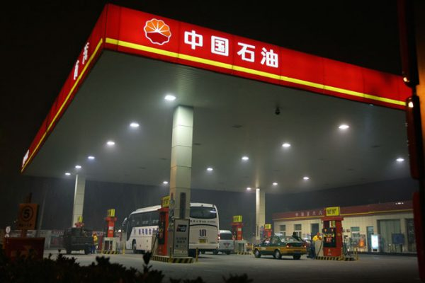 Station attendants serve customers at a PetroChina gas station in Beijing, 05 November 2007. (Frederic J. Brown/AFP/Getty Images)