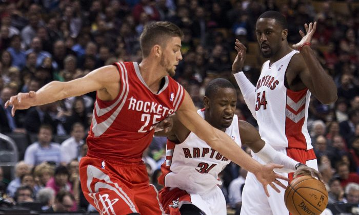 Toronto Raptors forward Terrence Ross, center, battles for the loose ball against Houston Rockets forward Chandler Parsons, left, as, Raptors forward Patrick Patterson, right, looks on during first-half NBA basketball action in Toronto, Wednesday, April 2, 2014. (AP Photo/The Canadian Press, Nathan Denette)