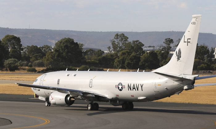 A U.S. Navy plane P-8 Poseidon takes off from Perth Airport on route to conduct search operations for missing Malaysia Airlines Flight MH370 in southern Indian Ocean, near the coast of Western Australia, Saturday, April 5, 2014. (AP Photo/Rob Griffith)