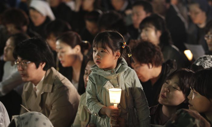 MAY 1: A girl holds a candle during a service to pay tribute to the victims of the sunken ferry Sewol  in Seoul, South Korea, Wednesday, April 30, 2014. Two weeks after the ferry sank off South Korea's southern cost, divers have recovered over 200 bodies from the wreckage, but they fought strong currents and floating debris inside the ship Wednesday as they searched for 90 passengers still missing.(AP Photo/Ahn Young-joon)
