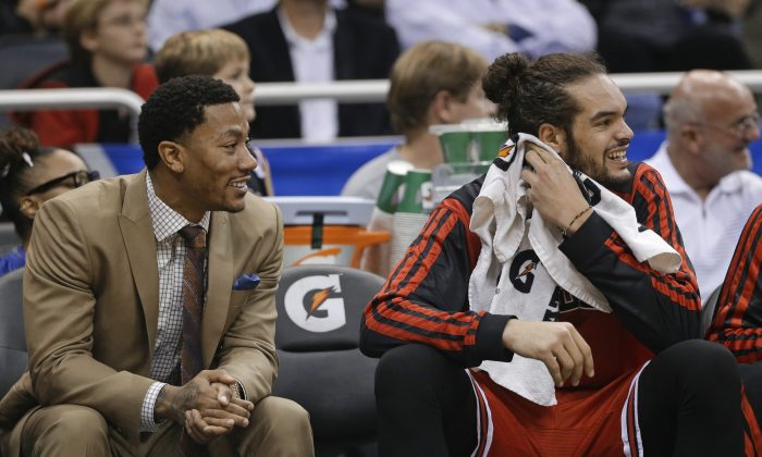 Chicago Bulls' Derrick Rose, left, watches play against the Orlando Magic with teammate Joakim Noah, right, during the first half of an NBA basketball game in Orlando, Fla., Wednesday, Jan. 15, 2014. (AP Photo/John Raoux)