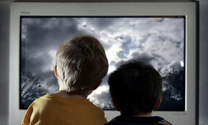 In this file photo illustration, two young child watch television at home. (Peter Macdiarmid/Getty Images)