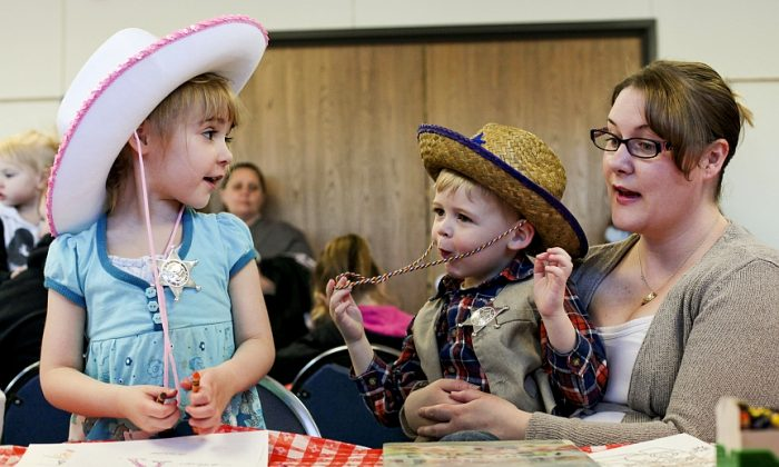 Christina Stein sits with her children, Tori, 5, and Eli, 3, as they draw during a wild west party at the St. Clair County Public Library in Port Huron, Mich., April 9, 2014. (AP Photo/The Port Huron Times Herald, Jeffrey Smith)